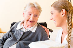 Nurse bringing supplies to woman in retirement home Royalty Free Stock Photography