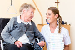 Nurse bringing supplies to woman in retirement home Royalty Free Stock Photo