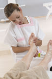 Nurse or care giver massaging foot of an elderly woman Stock Image