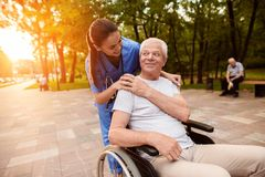The nurse laid her hand on the old man`s shoulder, who was sitting in a wheelchair and looking at him royalty free stock image