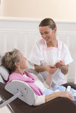 Nurse or caregiver assists an elderly woman with skincare Royalty Free Stock Image