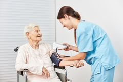 Caregiver makes blood pressure measurement in patient. Nurse or caregiver makes blood pressure measurement in old patient royalty free stock images