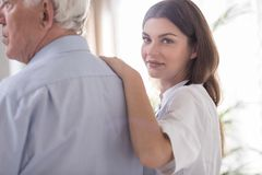 Nurse caring about elder man. Nurse caring about elder men in rest home Royalty Free Stock Image