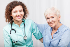 Nurse caring about senior lady stock images