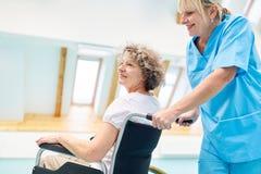 Nurse caring for a senior woman in a wheelchair stock photo