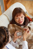 Nurse caring for unwell mature woman Royalty Free Stock Photo