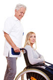 Nurse caring for woman. Nurse caring for a young woman in wheelchair Stock Image