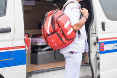 Nurse carry nursing bag on his back standing beside ambulance pr Royalty Free Stock Photos
