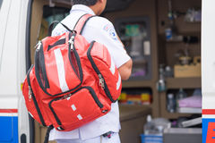 Nurse carry nursing bag on his back standing beside ambulance pr Royalty Free Stock Photography