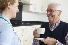 Nurse Chatting With Senior Man During Home Visit Royalty Free Stock Photo