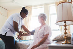 Nurse checking blood pressure of female patient Stock Photo