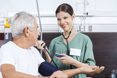 Nurse Checking Blood Pressure Of Male Patient In Rehab Center Stock Photo