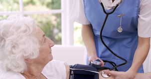 Nurse checking bloody pressure of senior woman stock footage