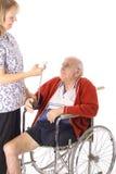 Nurse checking handicap mans stats Royalty Free Stock Image