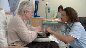 Nurse Checking On Senior Female Patient Having Chemotherapy