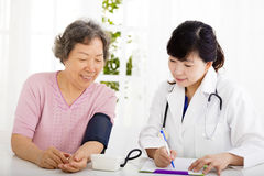 Nurse checking senior woman blood pressure Stock Images