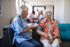 Nurse checking senior woman blood pressure at nursing home. Nurse checking senior women blood pressure while sitting on sofa in living room royalty free stock images