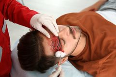 Nurse cleaning young man`s head injury in clinic. First aid stock photos