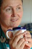Nurse on coffee break. Older, attractive nurse enjoying a cup of coffee during her break Royalty Free Stock Photos