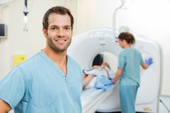 Nurse With Colleague Preparing Patient For CT Scan. Portrait of male nurse with colleague preparing patient for CT scan in examination room Royalty Free Stock Photo