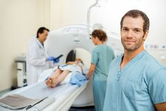 Nurse With Colleague And Radiologist Preparing. Portrait of male nurse with colleague and radiologist preparing patient for CT scan in examination room Royalty Free Stock Photography