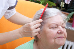 Nurse combing senior through her hair Royalty Free Stock Photography