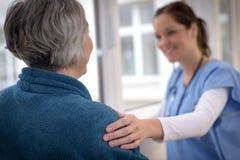 Nurse comforting elderly patient. Smiling female nurse comforting senior patient in hospital corridor Stock Photos