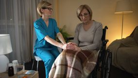 Nurse comforting old sick lady in wheel chair during recovery period, loneliness