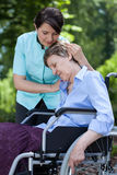 Nurse comforting an old woman on wheelchair royalty free stock image