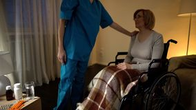 Nurse comforting senior woman in wheel chair assistance and help in nursing home. Nurse comforting senior women in wheel chair assistance and help in nursing stock photography