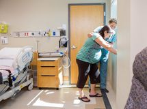 Nurse Comforting Tensed Pregnant At Window In. Mid adult female nurse comforting tensed pregnant women leaning on window sill in hospital room Stock Images