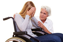 Nurse comforting woman. Nurse comforting young crying woman in wheelchair Stock Image