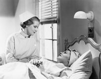 Nurse comforts a patient in a hospital bed, talking to each other stock photography