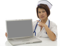 Nurse with computer screen. Attractive Asian medical professional pointing to blank screen on computer with room for your message Royalty Free Stock Photography