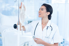 Nurse connecting an intravenous drip. In hospital room Stock Photo
