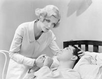 Nurse consoling a man in a hospital bed  (All persons depicted are not longer living and no estate exists. Supplier warranties tha Stock Image