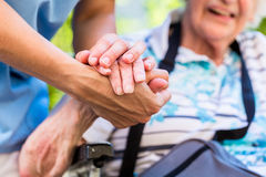 Nurse consoling senior woman holding her hand Stock Images