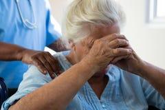 Nurse consoling senior woman at nursing home. Midsection of nurse consoling senior women at nursing home Stock Photos