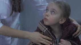 Nurse covering little sad girl with warm plaid, child missing home in hospital. Stock footage stock video footage