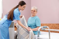 Nurse covering senior woman with plaid on bed in hospital ward royalty free stock images