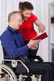 Nurse and disabled man reading book. Nurse and disabled men reading book, vertical Stock Photo