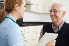 Nurse Discussing Medical Record With Senior Male Patient Royalty Free Stock Photography