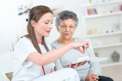 Nurse discussing medication with elderly woman. Nurse discussing medication with elderly women medication royalty free stock images