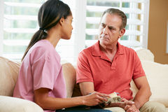 Nurse Discussing Records With Senior Male Patient Stock Photography