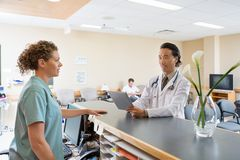Nurse And Doctor Conversing At Hospital Reception. Nurse and doctor with digital tablet conversing at hospital reception stock photos