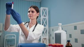 Nurse doctor holding a test tube, carefully examines it. Medicine, hospital, good girl nurse doctor in a white medical gown, with a stethoscope around his neck stock video