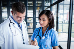 Nurse and doctor looking at files. In the hallway Stock Images