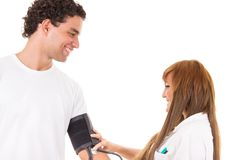 Nurse or doctor measures the blood pressure of a satisfied and s Royalty Free Stock Photos