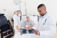 A nurse and a doctor are standing next to a patient with cancer. The doctor is holding her X-ray. The women is on the mend and glad of it. They are in a modern Royalty Free Stock Photography