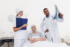 A nurse and a doctor are standing next to a patient with cancer. The doctor is holding her X-ray. The women is on the mend and glad of it. They are in a modern Stock Photos